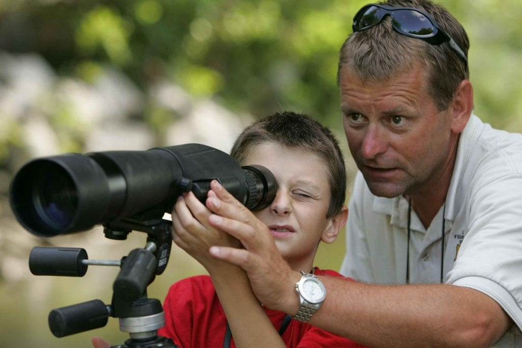 a boy looking through a spotting scope
