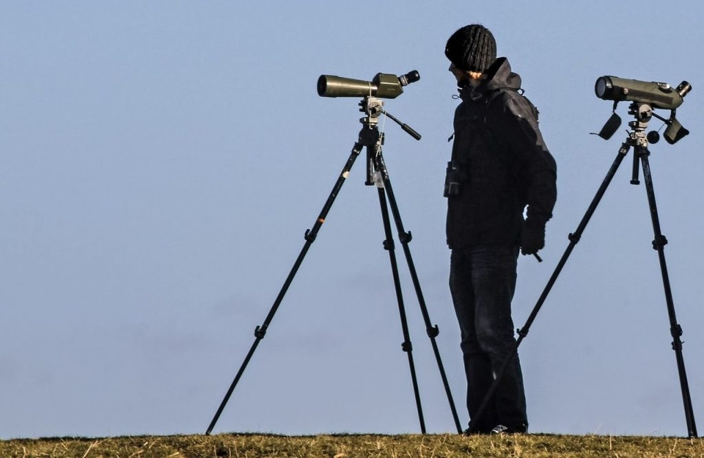 a man standing behind a spotting scope