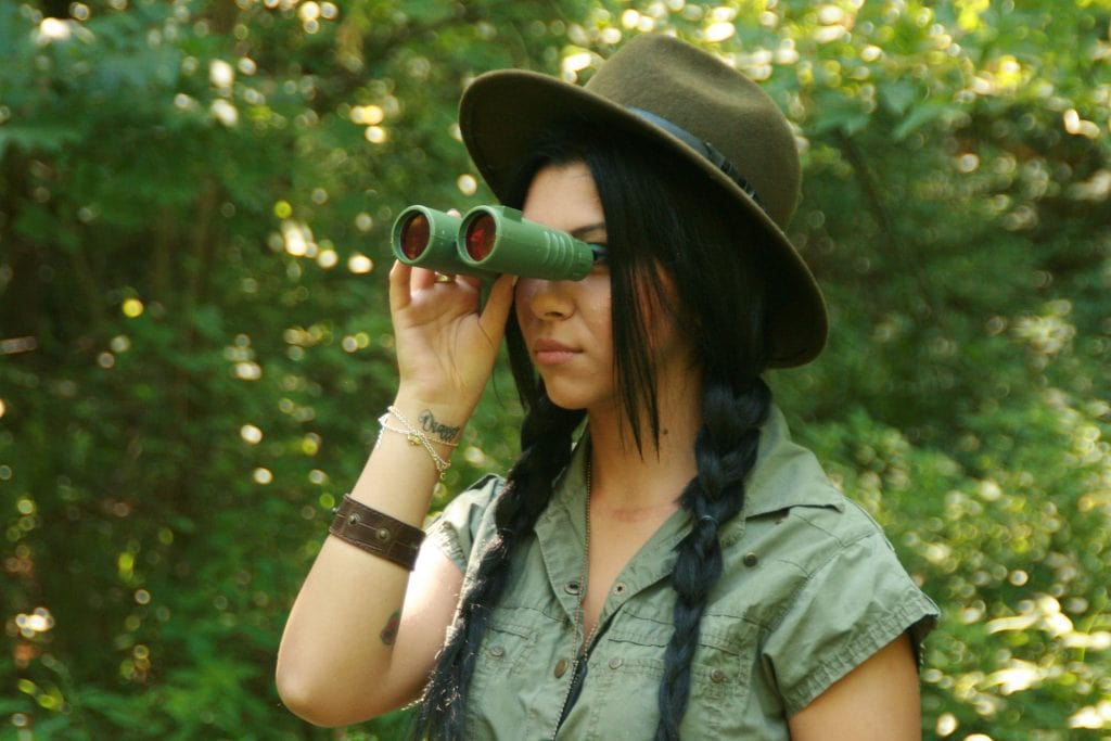young girl on a safari expedition using binoculars