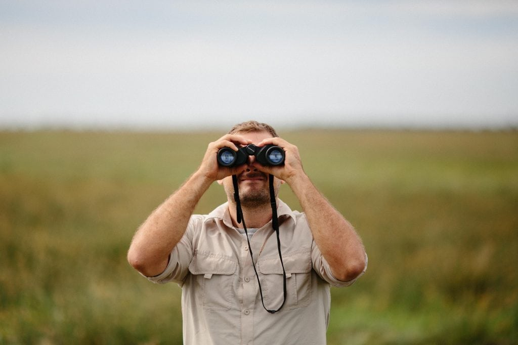 a man engrossed on the view from a binocular